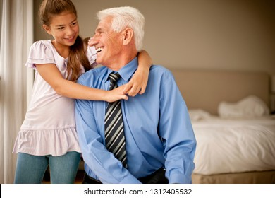 Senior man smiles up at his young granddaughter as she links her arms around his neck while they pose for a portrait.
