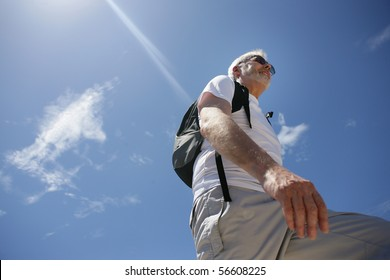 Senior man smiling with a backpack and sunglasses