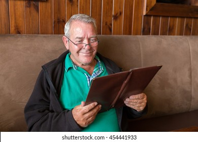 Senior man smiling big and reading a restaurant menu ready to order food