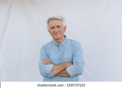 Senior man smiling with crossed arms