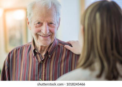 Senior man smiling as a family member comforts him in his retirement home.