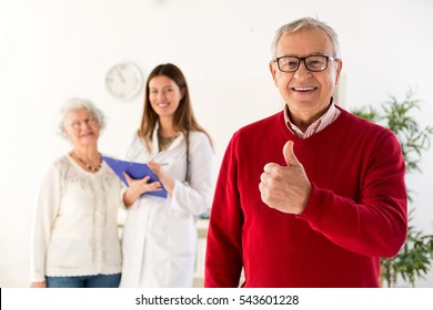 Senior man smiling with his wife and doctor in background at clinic