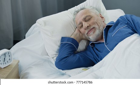 Senior man smiling while asleep in the morning, pleased pensioner lying in bed