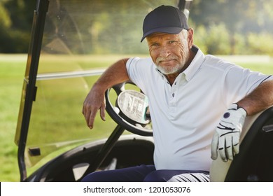 Senior man smiling while sitting in a cart enjoying a round of golf on a sunny day