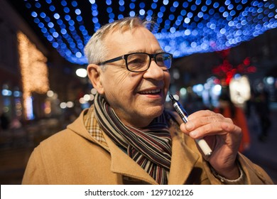 Senior man is smoking electronic cigarette in the city.