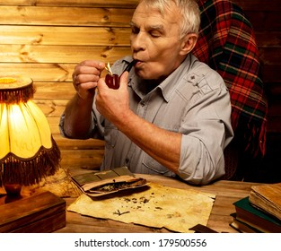 Senior man with smoking pipe in homely wooden interior