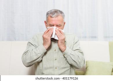 Senior man is sneezing into handkerchief.Senior man having flu