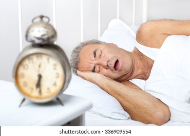 senior Man is snoring in bed. Health care concept