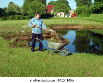 Senior man with spade and wheelbarrow repairing pond coast