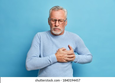 Senior man in spectacles presses hand to chest has heart attack suffers from unbearable pain closes eyes wears optical glasses poses against blue background. People age and problems with health