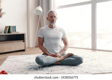 Senior man in sport clothing meditating while sitting on the floor in the lotus position at home
