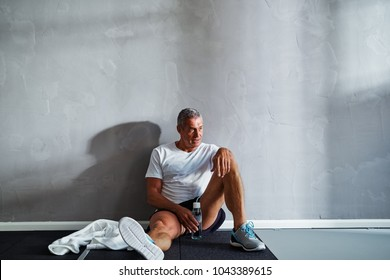Senior man in sportswear sitting on the floor of a gym drinking water while taking a break from a workout