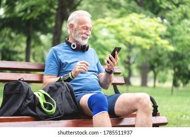 Senior man in sportswear using mobile phone fitness app sitting on park bench