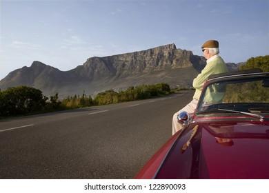 Senior man standing besides car in mountains
