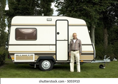 Senior man standing in front of his caravan