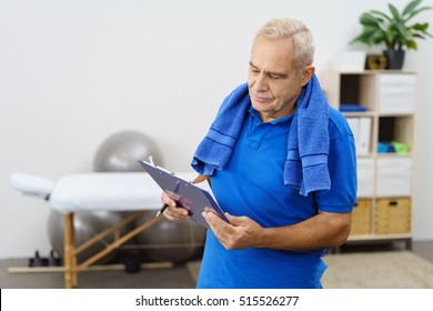 Senior man standing in a gym or physio room checking results on a clipboard