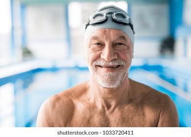 ecbc98f87b169 Senior man standing in an indoor swimming pool.