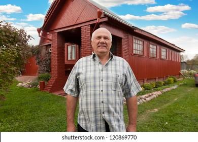 Senior man standing near red house