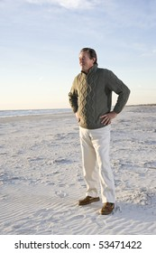 Senior man standing on beach with hands on hips