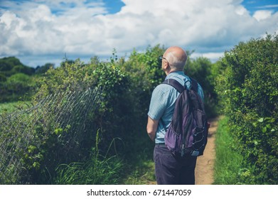 A senior man is standing outside in nature on a summer day