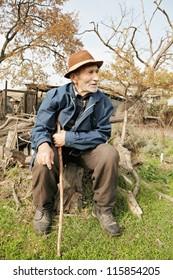 Senior man with stick sitting on stump outdoors