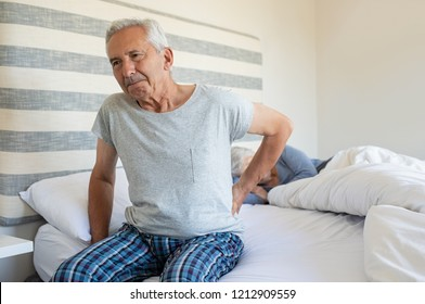Senior man suffering from back pain at home while wife sleeping on bed. Old man with backache having difficulty in getting up from bed. Suffering from backache and sitting on bed in the morning.