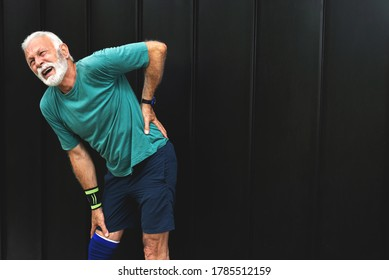 Senior man suffering with lower back pain during workout