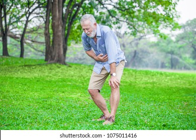 Senior man suffering from sick stomach or stomachache and vomiting outdoor in garden park . old elderly male drunk hangover and puke