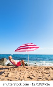Senior man sun bathing at the beach under parasol with waves, sea and sand