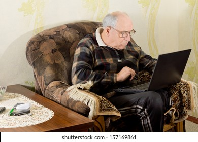 Senior man surfing the internet as he sits in a comfortable armchair in his living room with his laptop computer balanced on his lap
