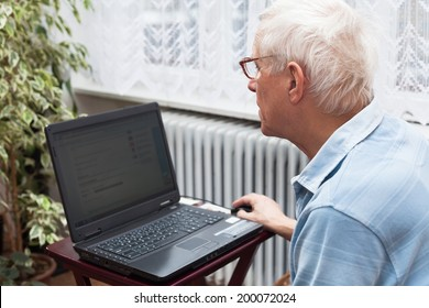 Senior man surfing on the internet at home.