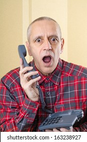 A senior man surprised by an incredible new on home phone