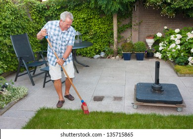 Senior man sweeping back garden on a sunny day