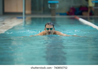Senior man swimming in frog style - Concept of sport and fun in swimming pool