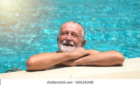 Senior man swimming in an outdoor swimming pool