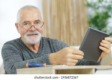 senior man with tablet checking how to fix a furniture