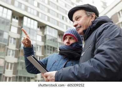 A senior man with a tablet in his hands asks for directions from a stranger. Girl shows him with finger the right direction