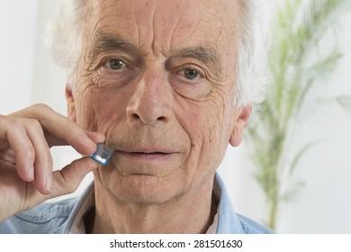 Senior man tacking  homeopathic medicine