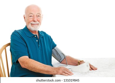 Senior man taking his blood pressure at home on the kitchen table.  White background.