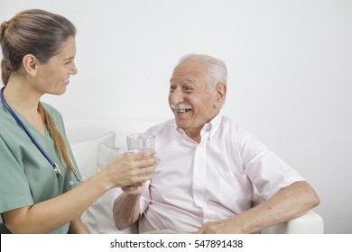 Senior man taking his medication under the guidance of his nurse in retirement home