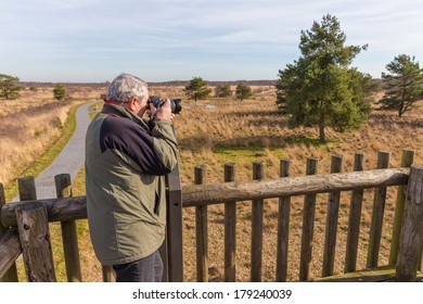 Senior man taking photos from an observation post