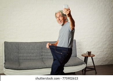 Senior Man Taking Selfie, Showing Her Weight Loss