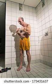 Senior man taking a shower in bathroom. Wearing yellow swimming trunks.