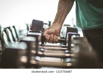 Senior man taking weight. Close up. Focus is on hand.