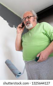 Senior man talking on the cell phone while painting the wall
