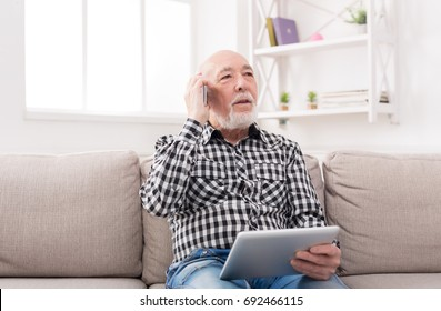 Senior man talking on phone and using tablet, sitting on sofa at home. Modern technology, communication concept