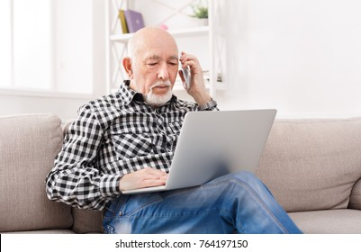 Senior man talking on phone and using laptop, sitting on sofa at home. Modern technology, communication concept, copy space