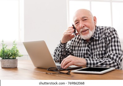 Senior man talking on phone and using laptop, sitting at table at home. Modern technology, communication concept, copy space