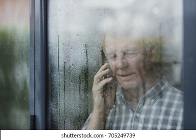 Senior man is talking to someone on the phone in his home. He is standing at the window and it is raining outside.