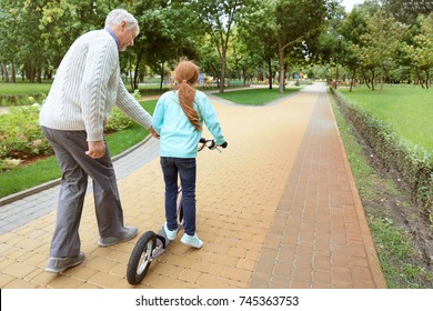 Senior man teaching his granddaughter how to ride kick scooter in park